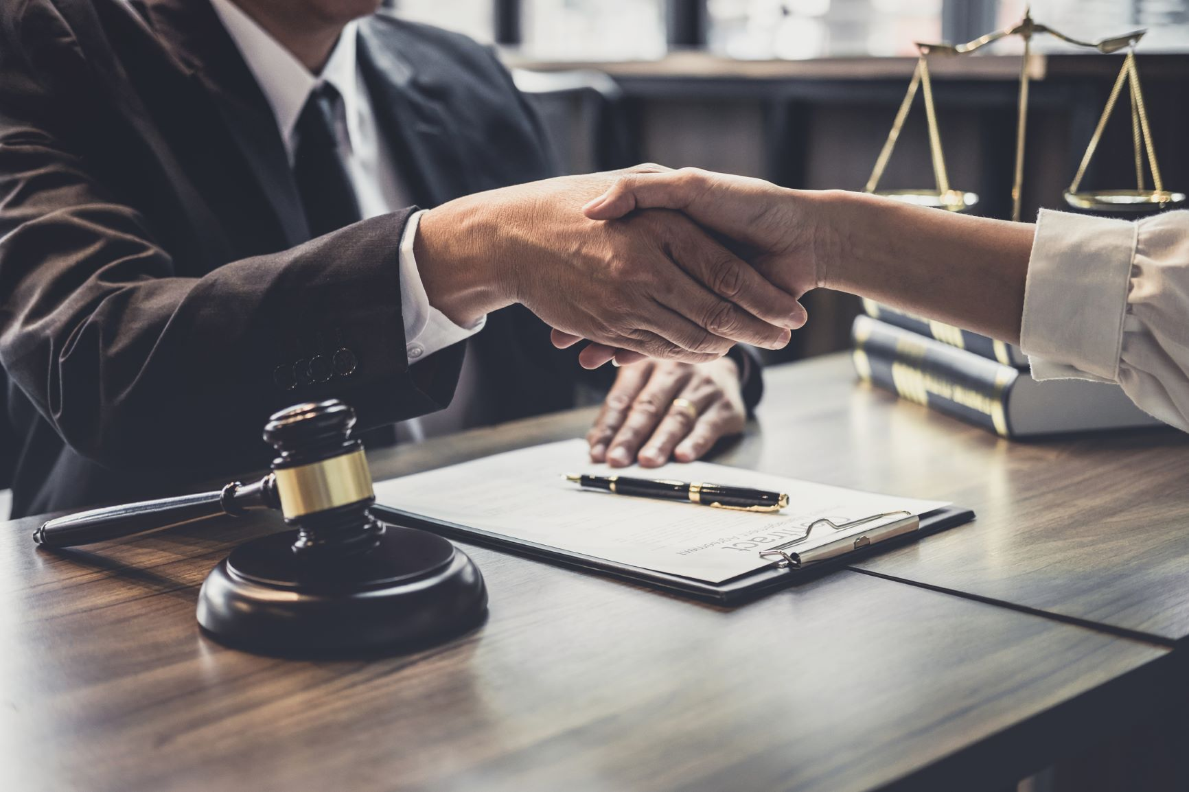 attorney and client meet and shake hands over desk in law firm office