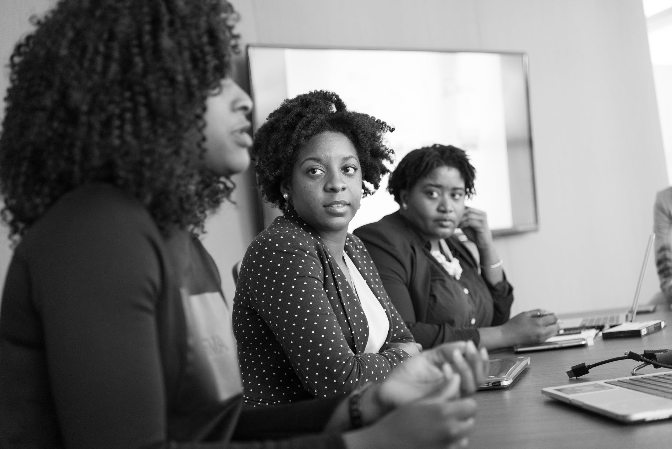 Two women listen as a third speaks about client retention at a table in a conference room.