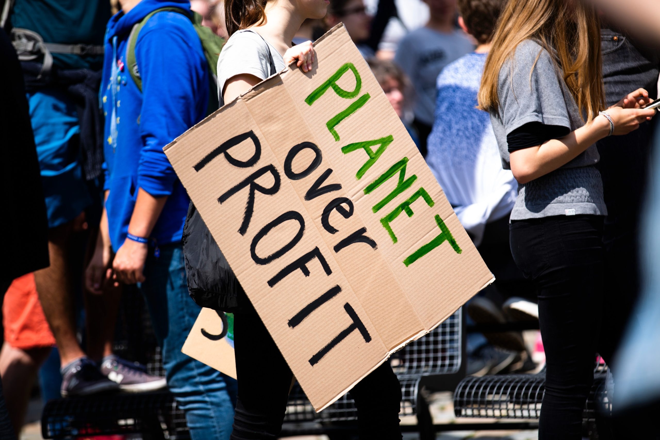 """Eco friendly marketing. A group of environmental protesters, one carrying a cardboard sign reading, """"Planet over Profit""""."""