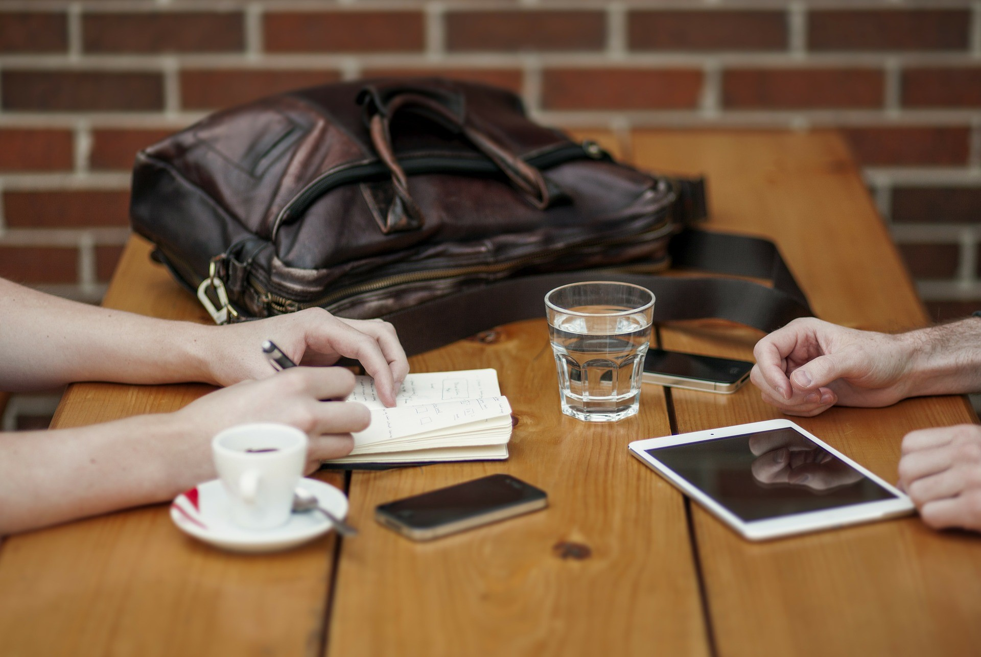 Two people sit opposite each other in a sales conversation at a table with drinks, mobile devices, a bag and a notebook arrayed on top.
