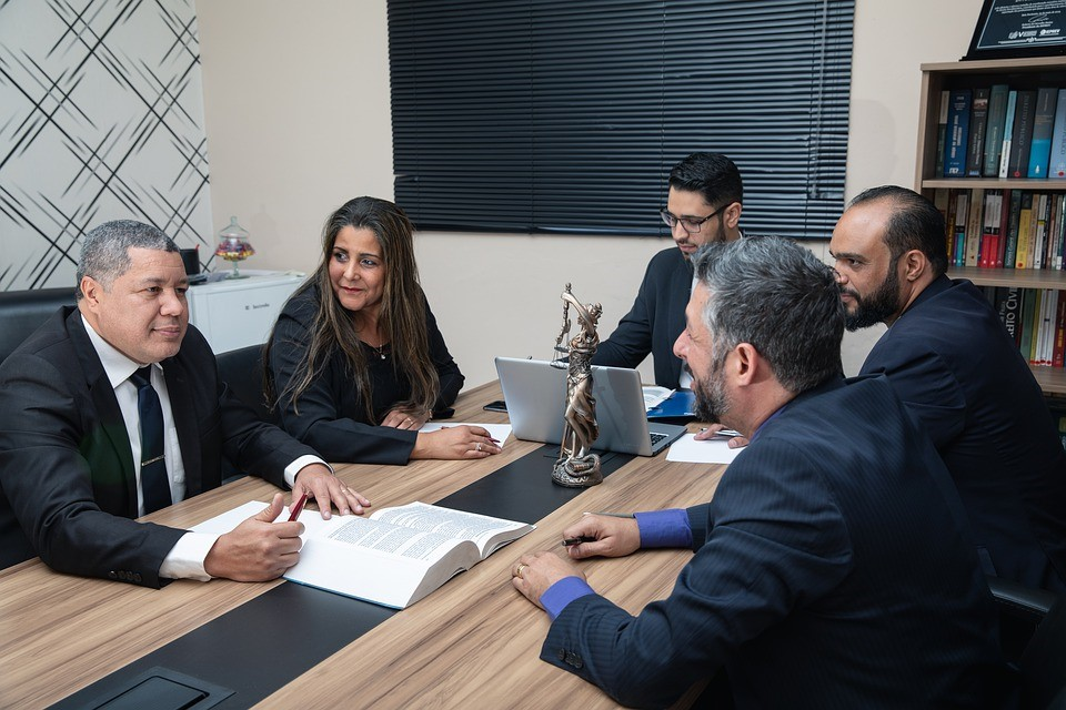A group of lawyers have a management meeting at a long table in a law office.