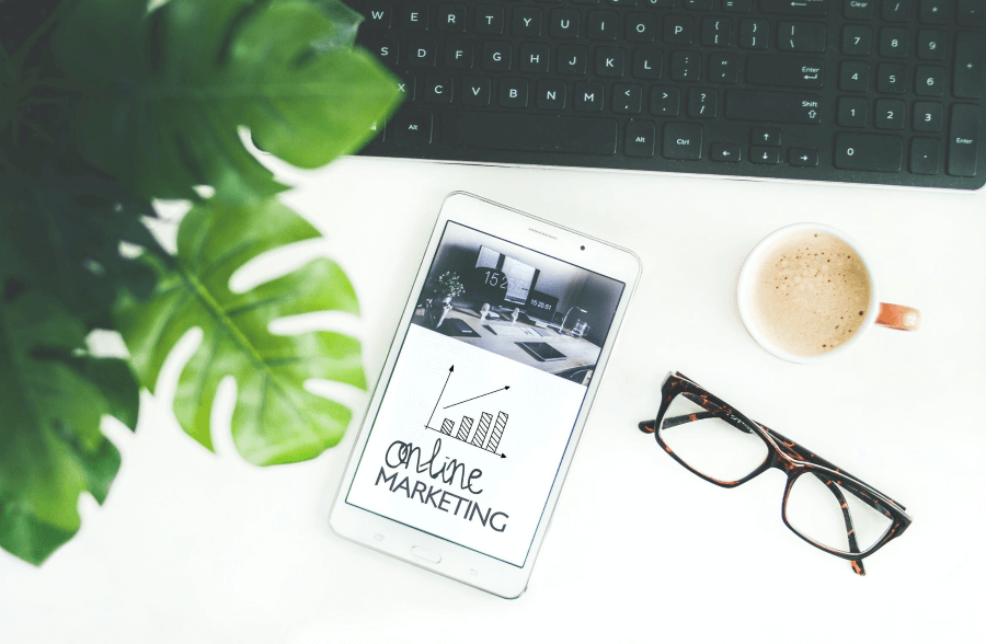 """Eyeglasses, a mug of coffee, and a keyboard laying a tabletop around a white phone whose screen displays a graph and reads, """"Online Marketing""""."""