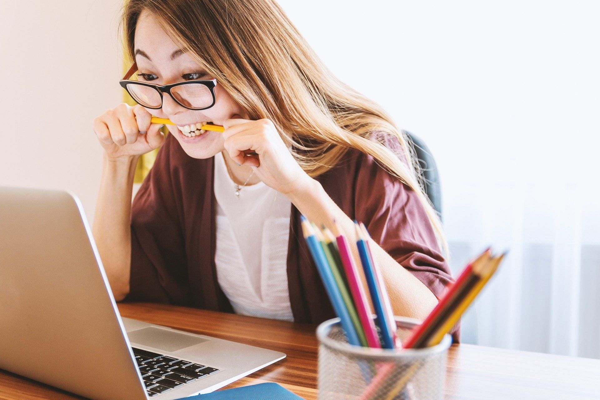 A woman bites on a pencil while looking anxiously at her laptop disabling social media comments