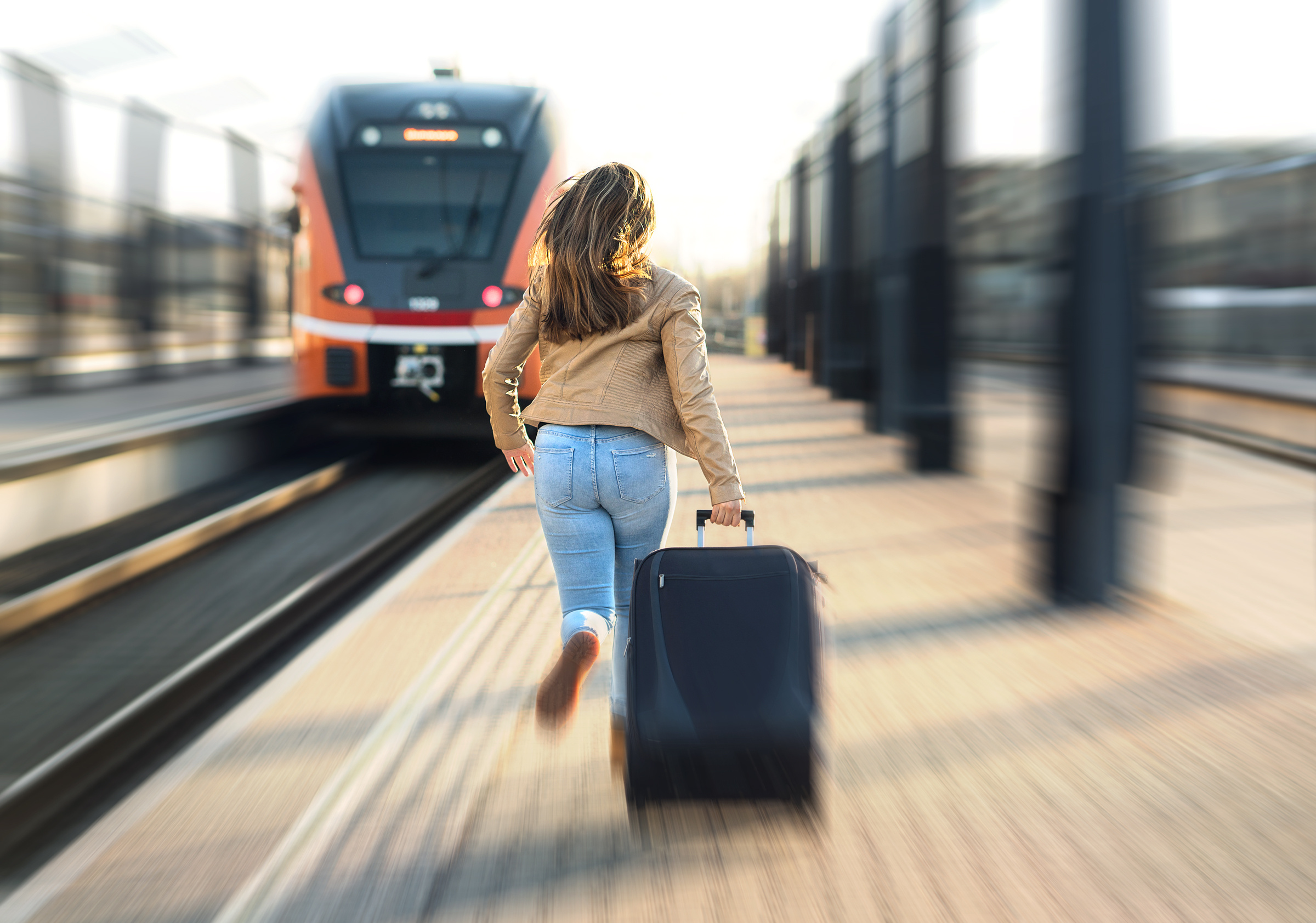 woman is late for train and rushes down the platform to catch it