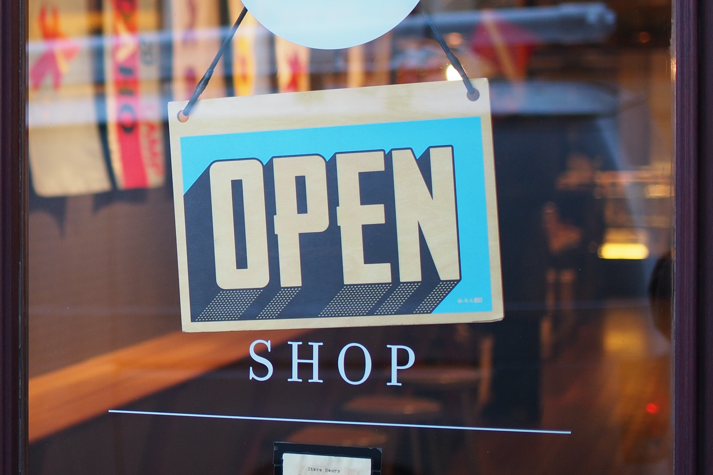 """A white and blue """"Open"""" sign hangs in a shop window."""