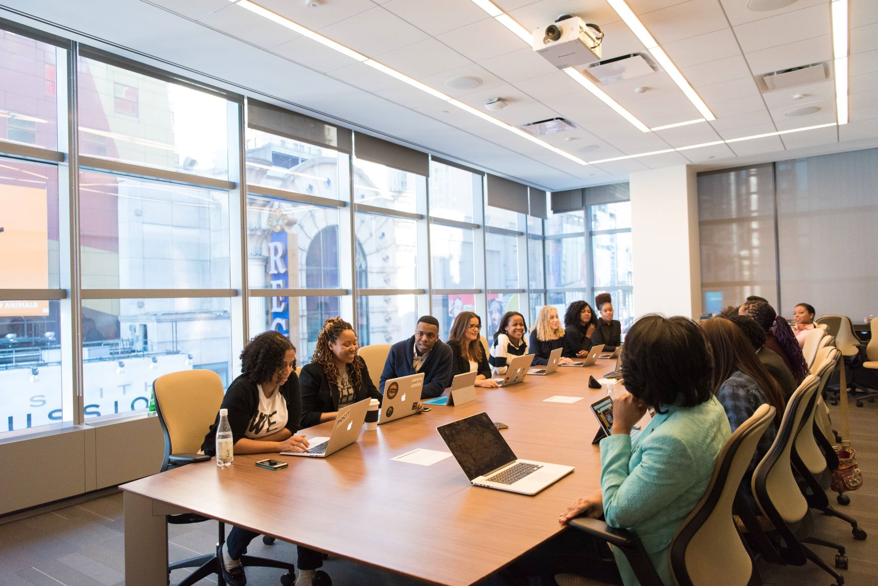 A large number of people sitting at a conference table in a meeting.