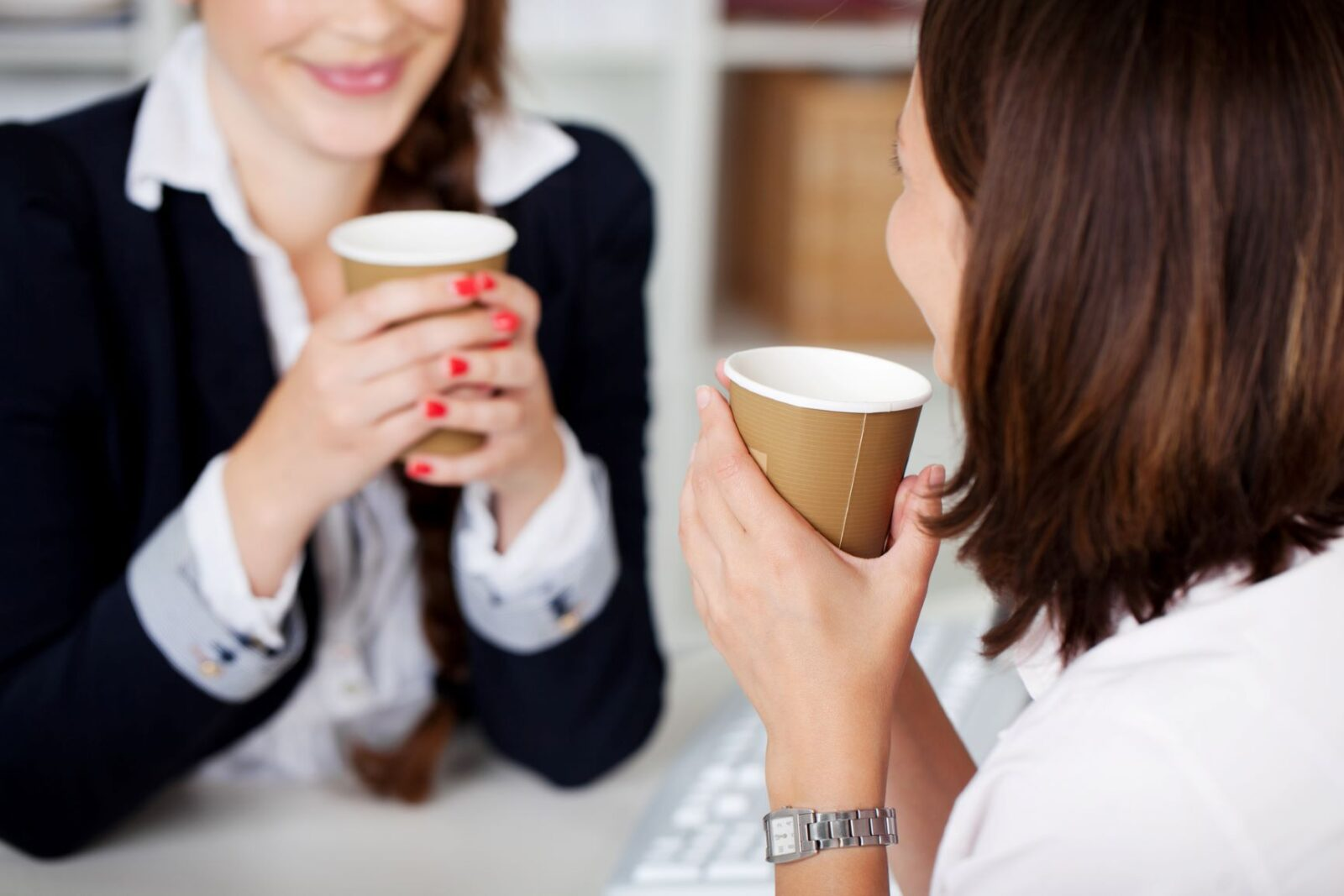Over-the-shoulder shot of a client drinking coffee from a paper cup while having a friendly conversation with an attorney, seated opposite.