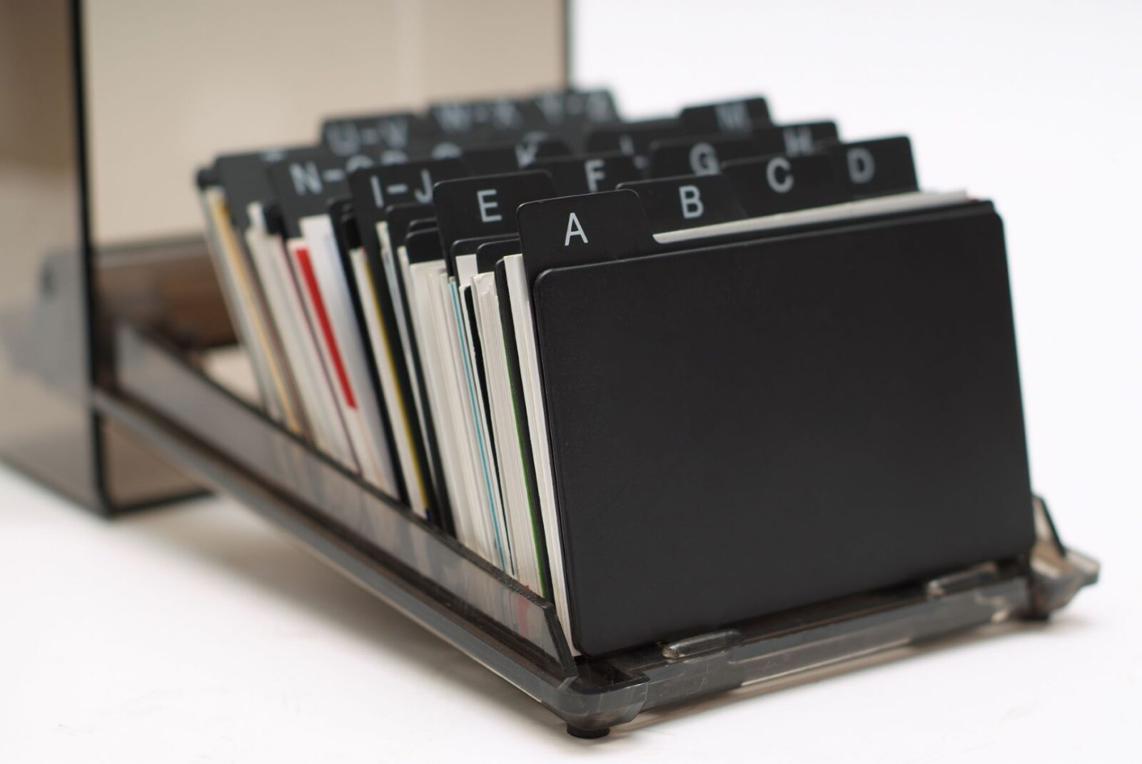 Close-up view of a Rolodex, alphabetically organizing index cards with the names and contact information of different sales leads.